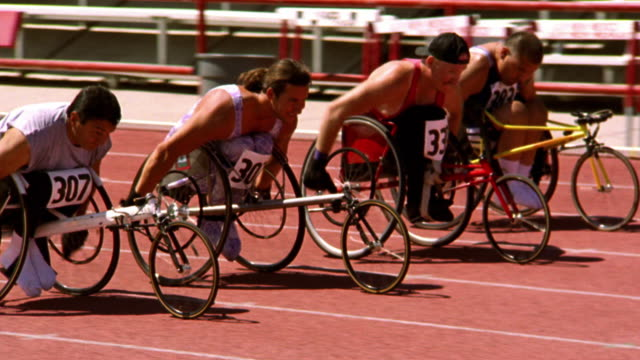 slow motion pan group of men in wheelchairs racing on track - sportsperson stock videos & royalty-free footage