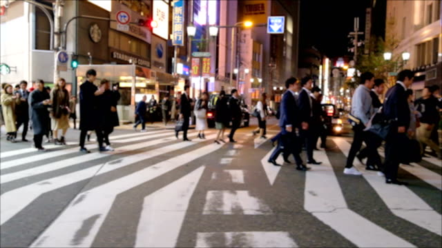 4k slow motion: group of salary man across the road at zebra crosswalk after hang out party - pedestrian crossing stock videos & royalty-free footage