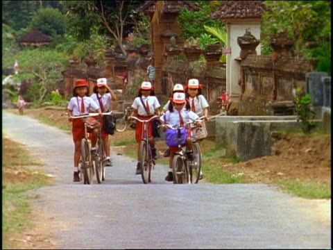 slow motion group of schoolgirls in uniform riding bicycles on country road towards camera / Bali