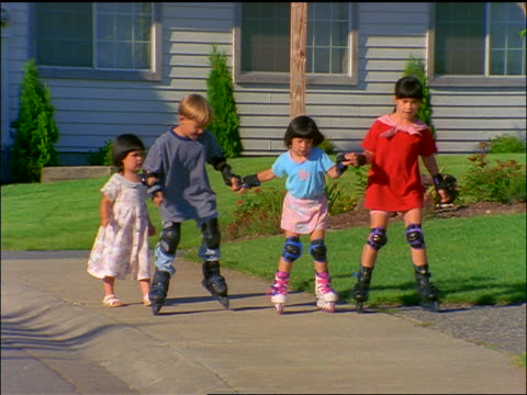 slow motion group of small children holding hands + inline skating on sidewalk towards camera