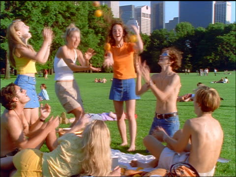 slow motion group of young people playing catch with fruit in sheep's meadow of central park / nyc - sheep meadow central park stock videos and b-roll footage