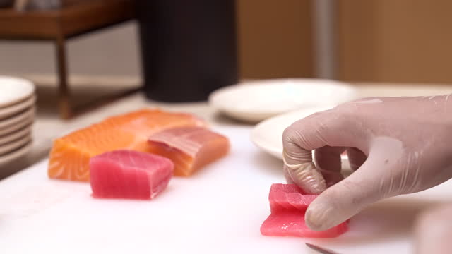4k uhd slow motion hand held: close up chef's hand cutting raw salmon and tuna to serve as sashimi, japanese groumet cuisine. - cutting stock videos & royalty-free footage