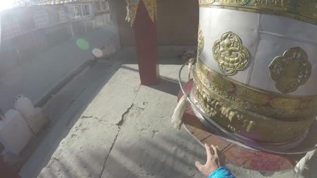 Slow motion POV of hand on prayer wheel
