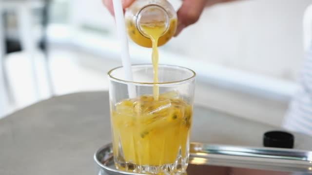 slowmotion hand häll passionsfrukt drink i ice i glasögon - passionsfrukt bildbanksvideor och videomaterial från bakom kulisserna