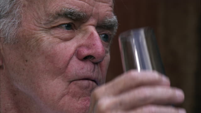 Slow motion handheld close-up shot of an elderly man drinking wine