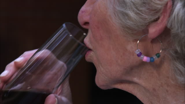 slow motion handheld close-up shot of an elderly woman drinking wine - vino video stock e b–roll