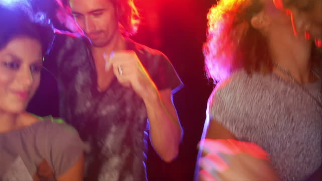 Slow motion handheld four people dancing amid colored lights