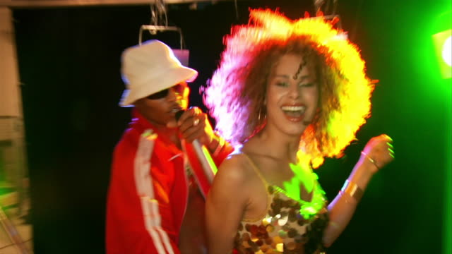 Slow motion handheld man wearing tracksuit and hat singing into microphone, gesturing, young woman wearing sequined minidress dancing beside him