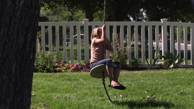 slow motion handheld shot of a child riding a tree swing - picket fence stock videos and b-roll footage