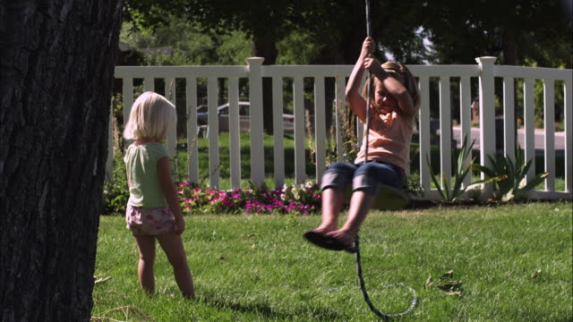slow motion handheld shot of a child swinging on a tree swing while another one looks on - rope swing stock videos & royalty-free footage