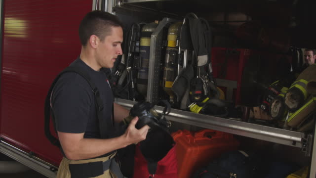 slow motion handheld shot of fireman doing routine maintenance check on protective gear - fire station stock videos & royalty-free footage