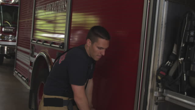 slow motion handheld shot of fireman doing routine maintenance on fire truck in fire station - feuerwache stock-videos und b-roll-filmmaterial