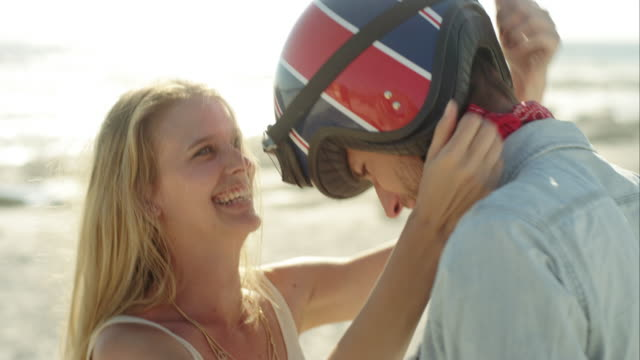 CS slow motion handheld young couple embracing and playing around by beach
