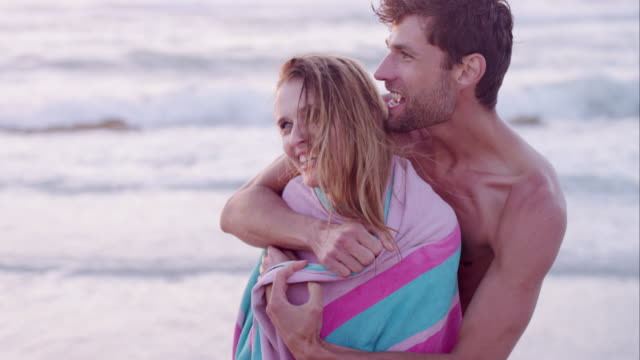 cs  slow motion handheld young man wrapping young woman in towel and embracing - タオルにくるまる点の映像素材/bロール