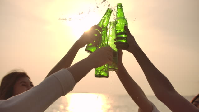 vídeos de stock e filmes b-roll de slow motion hands toasting beer bottles on beach at sunset, winning, celebration - beer alcohol