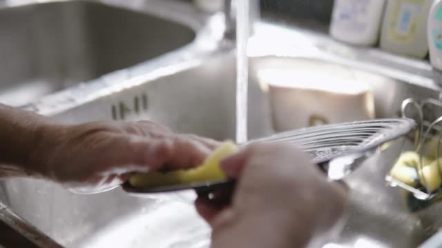 Zeitlupe: Hände der senior waschen Schale in ein Waschbecken zu Hause.