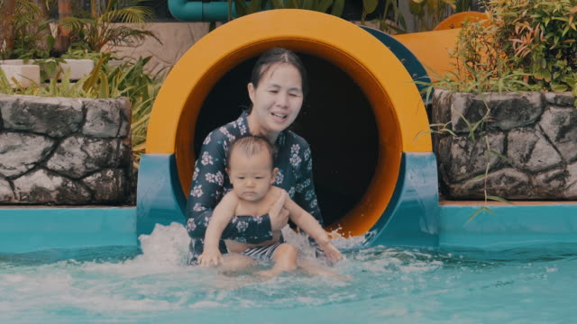 slow motion : happy mother and her baby boy on water park slides - 6 11 months stock videos & royalty-free footage