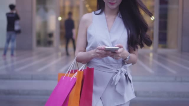slow motion : happy young girl is walking in a department store and texting a message on a smartphone. - fare spese video stock e b–roll