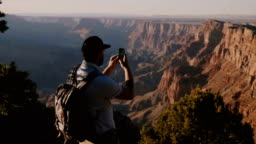 Slow motion happy young tourist man with backpack taking smartphone photo of epic summer sunset over Grand Canyon USA.