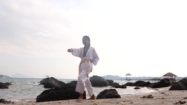 vidéos et rushes de slow motion hd: pratiquer les arts martiaux en plein air sur la plage - karaté