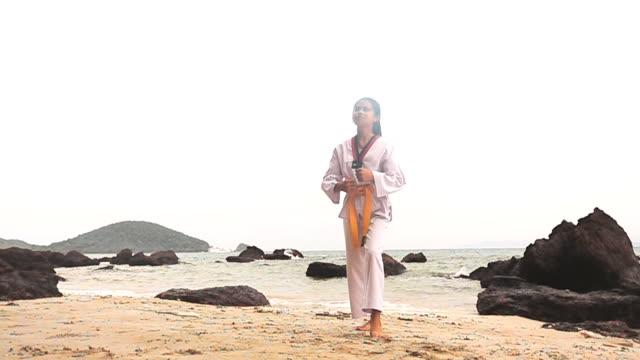 vídeos de stock, filmes e b-roll de câmera lenta hd: praticando artes marciais ao ar livre na praia - karate