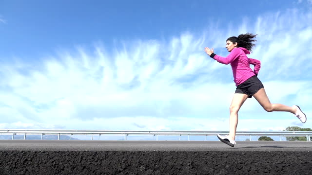 slow motion hd video of adult woman running on asphalt road - whole stock videos & royalty-free footage