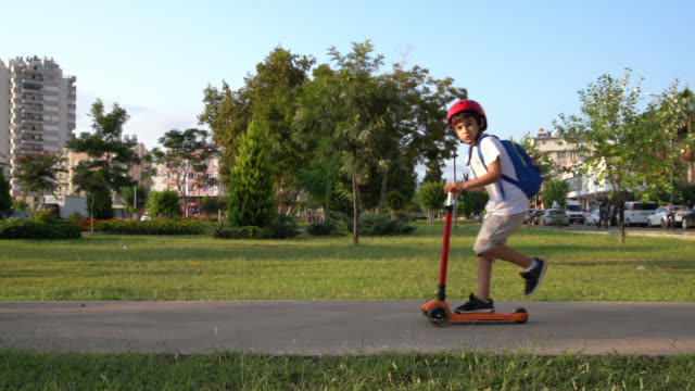 slow motion hd video of little school boy riding push scooter in public park - push scooter stock videos and b-roll footage