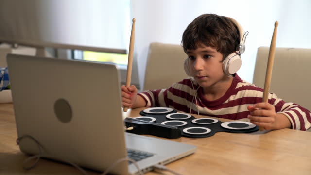 slow motion hd video of schoolboy learning how to play drum by watching video on internet - selimaksan stock videos & royalty-free footage