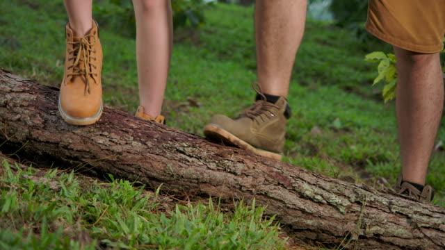 vídeos y material grabado en eventos de stock de 4k cámara lenta. el y ella están limpiando la suela del zapato, frotando los zapatos con un tronco quitando la suciedad de la suela del zapato. - planta del pie