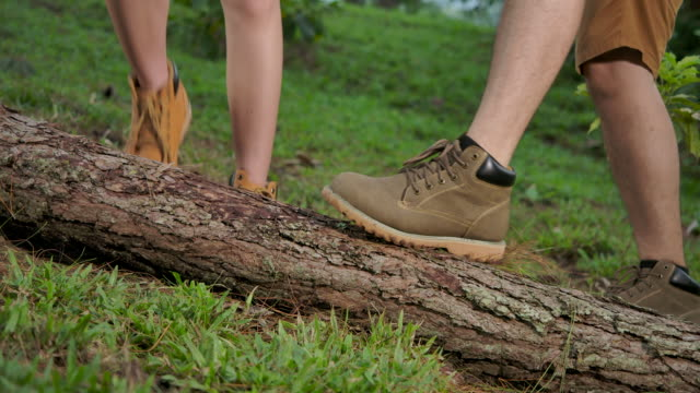 4k slow motion. he and she are cleaning the sole of the shoe, by rubbing shoes with a log removing dirt from the sole of the shoe. - human limb stock videos & royalty-free footage