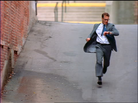slow motion high angle businessman running towards camera + looking at watch