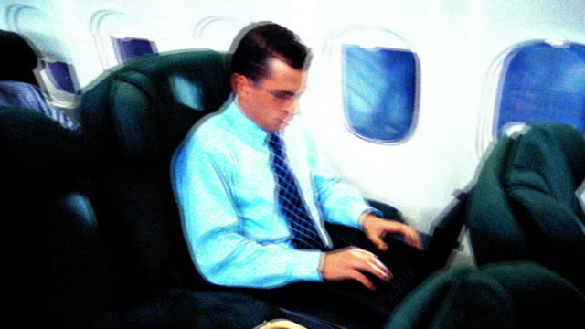 stockvideo's en b-roll-footage met overexposed slow motion high angle businessman typing on laptop on airliner / cup of coffee next to him - overhemd en stropdas
