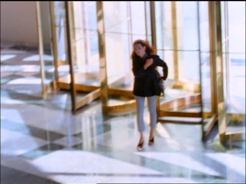 vídeos y material grabado en eventos de stock de slow motion high angle businesswoman entering office building through revolving door + rushing - puerta giratoria