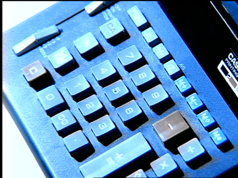 BLUE slow motion high angle close up finger of man punching numbers on adding machine