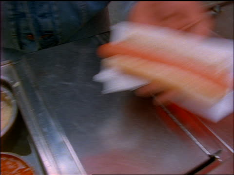 slow motion high angle close up food vendor prepares hot dog on nyc street / hands hot dog to customer - ketchup stock videos and b-roll footage