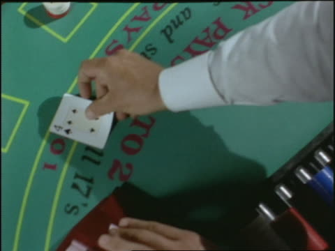 slow motion high angle close up hands of card dealer dealing cards to betting players at blackjack table