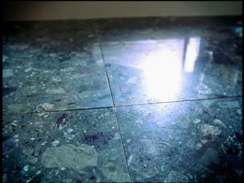 slow motion high angle close up piggy bank falling + smashing on marble surface with coins flying out on impact