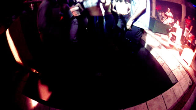 overexposed slow motion high angle crane shot people dancing on dance floor of nightclub with flashing lights - overexposed video stock e b–roll