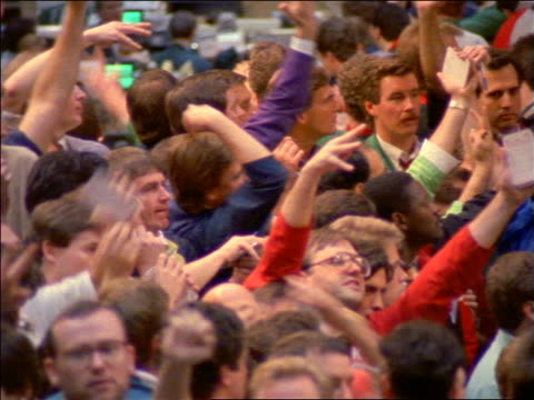 slow motion high angle pan crowd of stock traders signal with hands / chicago board of trade or mercantile exchange - seller stock videos and b-roll footage