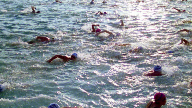 slow motion high angle crowd of swimmers racing in ocean / iron man competition, hawaii - triathlon stock videos & royalty-free footage