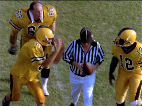 slow motion high angle football players arguing with referee