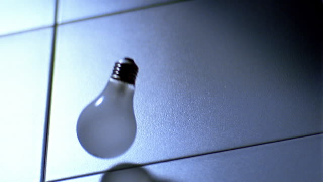 slow motion high angle MS light bulb falling on tiled floor + bouncing