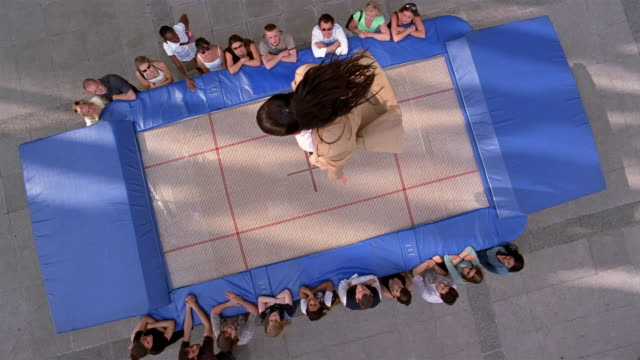 Slow motion high angle long shot woman bouncing up and down on trampoline with crowd watching