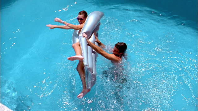 Slow motion high angle man flipping woman on raft over in swimming pool