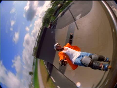 semi-fisheye slow motion high angle man on inline skates performing backflip stunt on half-pipe ramp - blade stock videos & royalty-free footage
