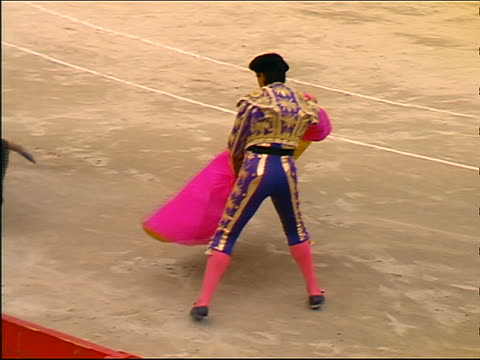 slow motion high angle matador stepping aside as bull charges through pink + yellow cape - 雄牛点の映像素材/bロール