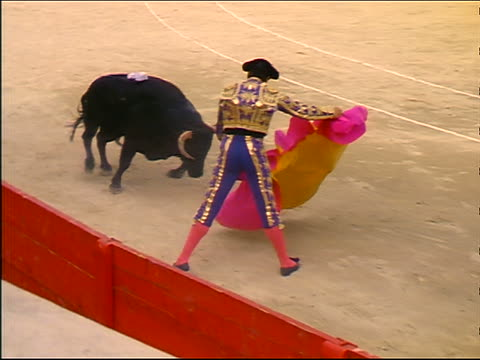 slow motion high angle matador stepping aside as bull charges through pink + yellow cape - pflanzenfressend stock-videos und b-roll-filmmaterial
