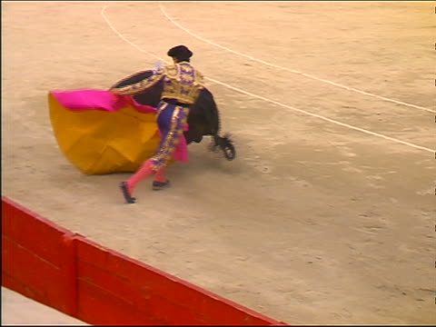 slow motion high angle matador stepping aside as bull charges through pink + yellow cape - cape stock videos & royalty-free footage