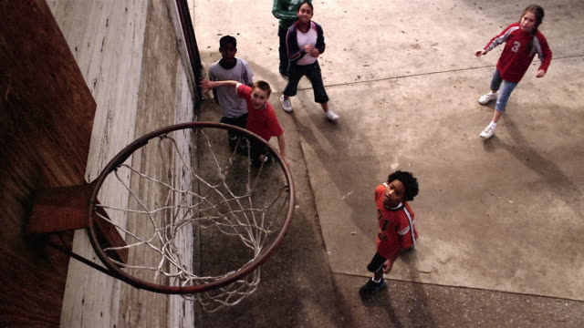 Slow motion high angle medium shot boy shooting basketball and missing shot / boys fighting for rebound