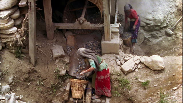 slow motion high angle medium shot female workers loading rocks into baskets / nepal - 炭鉱点の映像素材/bロール